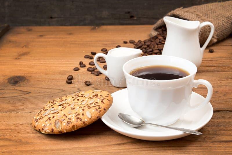 Tasse de café avec les biscuits, grains de café rôtis dans le sac photographie stock