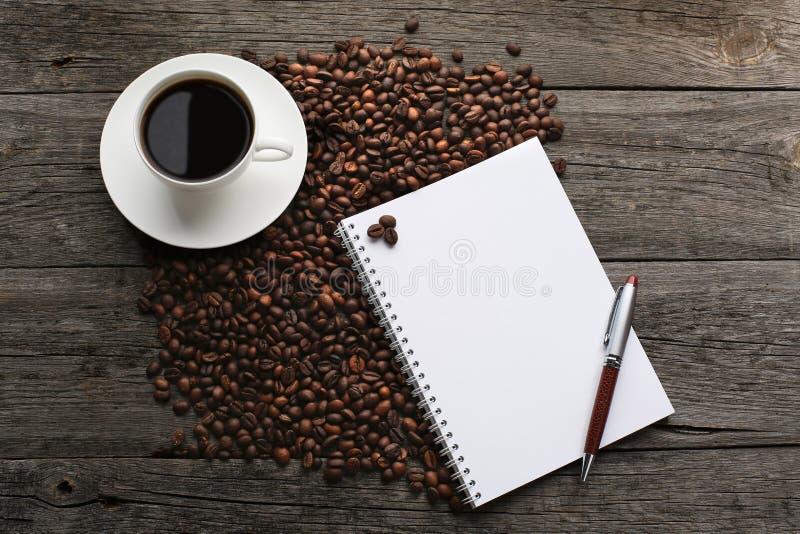 Tasse de café avec les grains de café et le carnet photographie stock