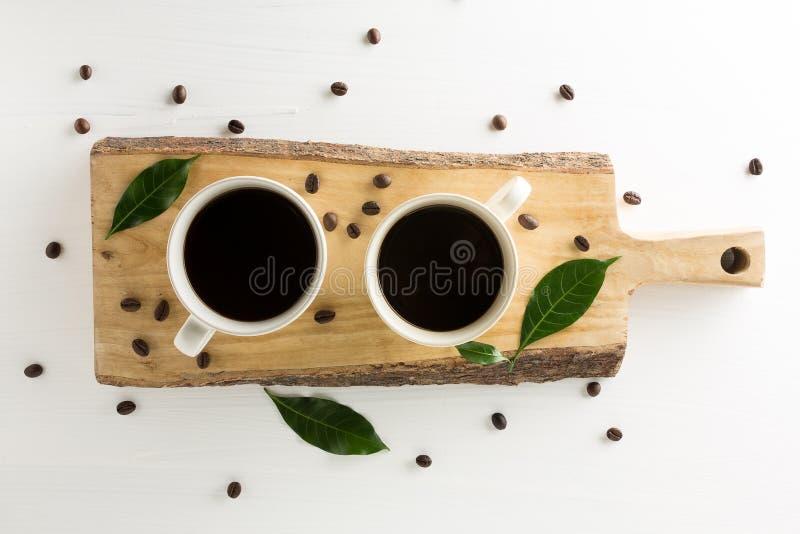 Tasse de café avec les grains de café, le conseil en bois et la feuille sur le blanc image stock