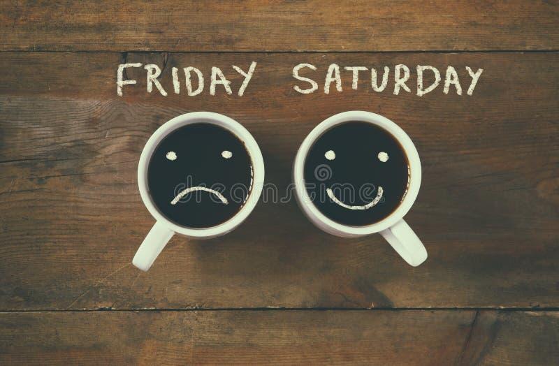 Tasse de café avec les visages tristes et heureux à côté du fond d'expression de vendredi samedi Vintage filtré Concept heureux d image libre de droits