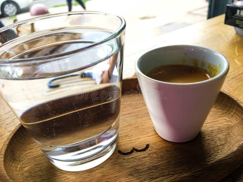 Tasse de café avec un verre de l'eau sur un plateau avec la cuillère photo libre de droits