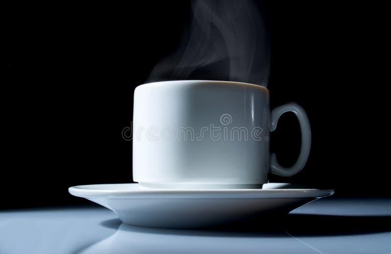 Tasse de café avec une belle fin de fumée sur un fond noir photos stock