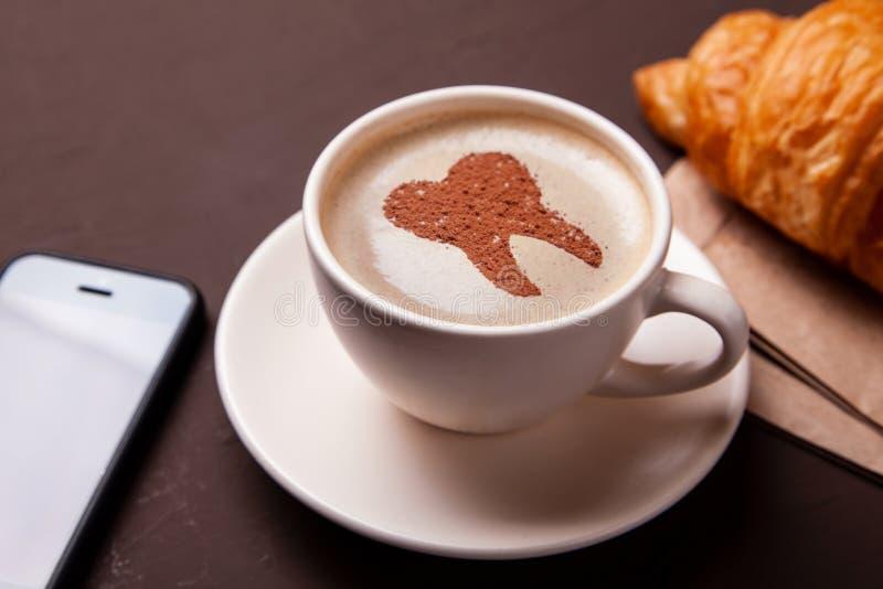 Tasse de café avec une dent sur la mousse Le café abîme des dents et les rend jaunes Café de matin ou pause-café avec le croissan images libres de droits