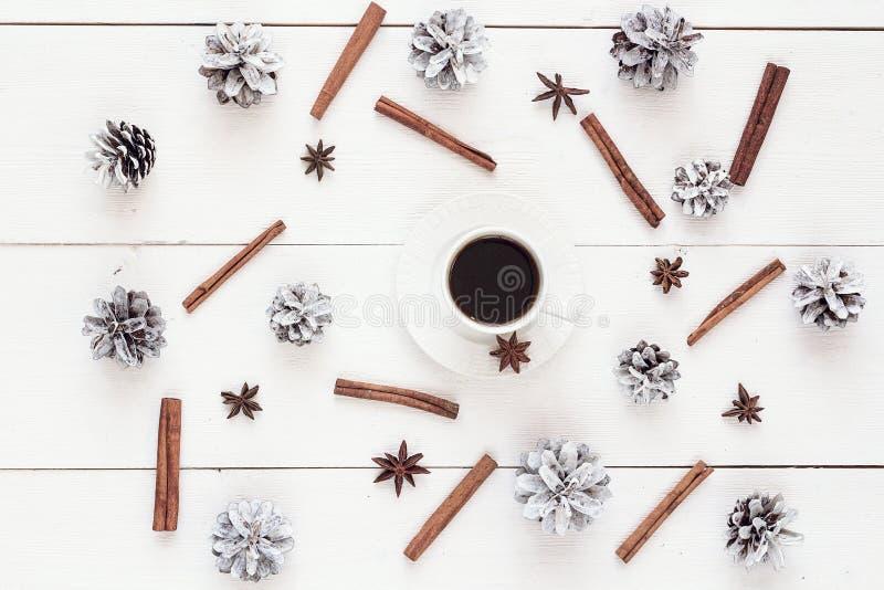 Tasse de café blanc avec des cônes de pin, des bâtons de cannelle et l'anis d'étoile images stock