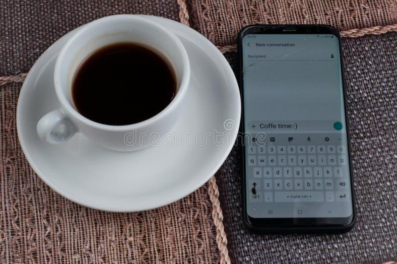 Tasse de caf? blanc avec le t?l?phone portable sur la table Temps de caf? photographie stock libre de droits