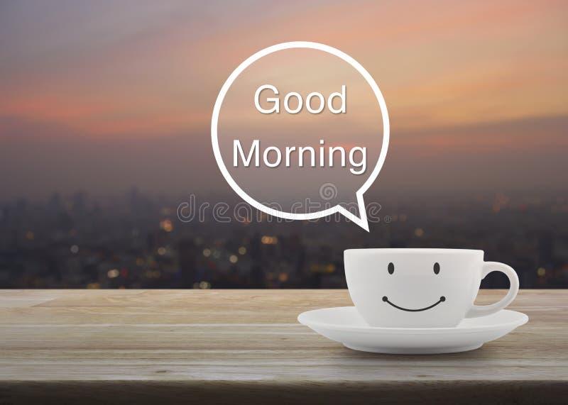 Tasse de café blanc heureuse de sourire sur la table en bois au-dessus du paysage urbain de tache floue photos libres de droits