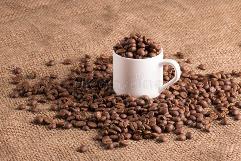 Tasse de café blanc sur le tissu texturisé complètement du grain d'arome, haricots photo libre de droits