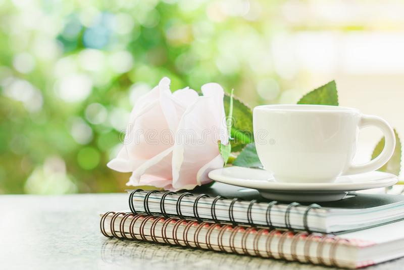 Tasse de café blanc sur les carnets de notes à spirale avec la fleur douce de rose de rose photo stock