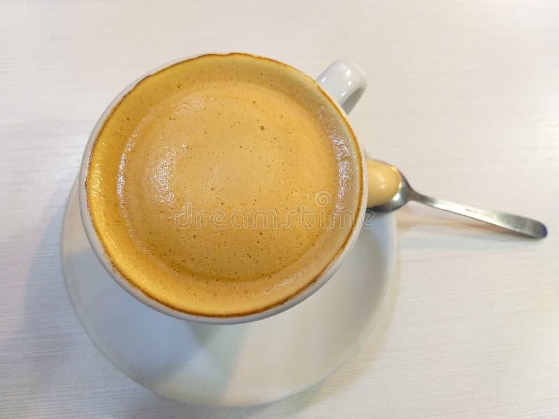 tasse de café blanche avec du lait une cuillère à café métallique sur une soucoupe blanche sur une table blanche photo stock