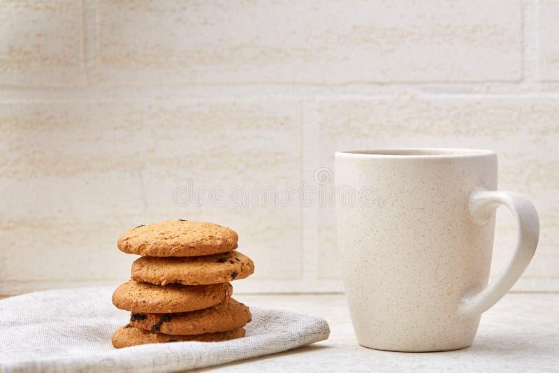 Tasse de café blanche en gros plan avec les gâteaux aux pépites de chocolat délicieux sur le fond blanc, vue supérieure photos stock