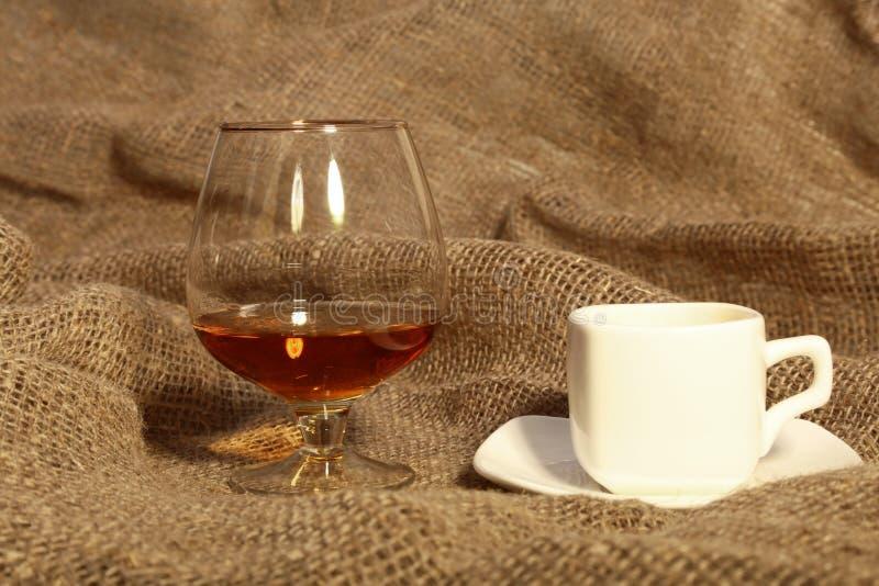 Tasse de café blanche et cognac ou eau-de-vie fine dans des verres sur vieux renvoyer de textile image stock