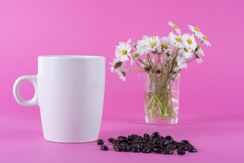 Tasse de café blanche et grains de café et fleur brouillée de marguerite images stock