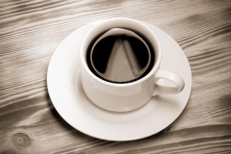 Tasse de café blanche sur la nouvelle table en bois toned images stock