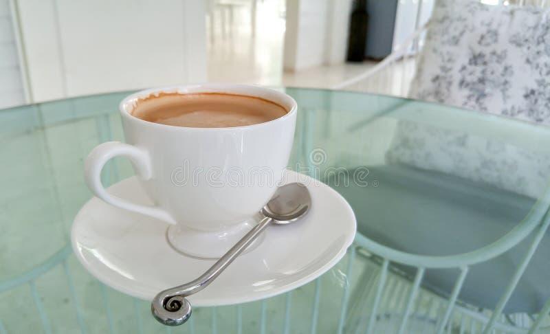 Tasse de café blanche sur le Tableau en verre utilisé comme calibre photographie stock libre de droits