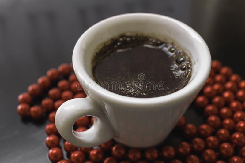 Tasse de café blanche sur une surface foncée entourée par les perles rouges images libres de droits