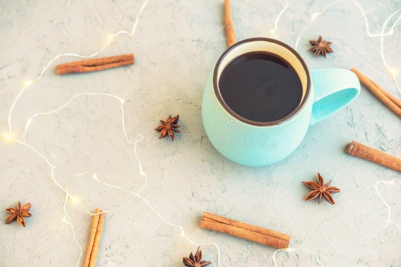 Tasse de café bleue sur le fond concret gris Bâtons de cannelle, étoiles d'anis et guirlande Automne et hiver confortables de boi photographie stock