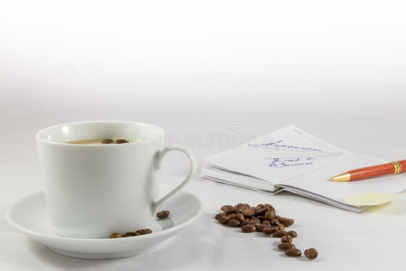Tasse de café, carnet, stylo et grains de café sur le fond blanc photo stock