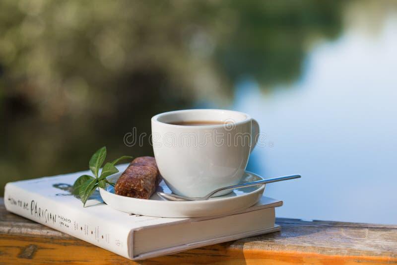 Tasse de café chaud pour le brackfast et de livre avec des barres sur le balcon en bois près du fond de rivière et de montagne photo libre de droits
