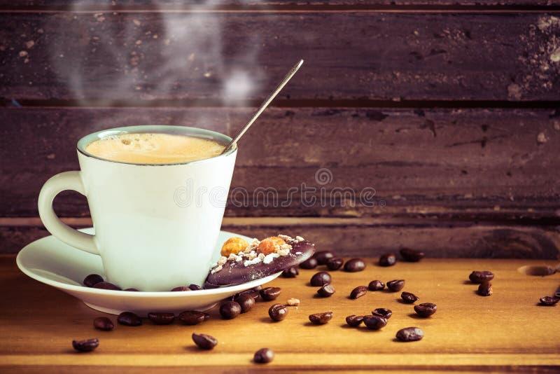 Tasse de café chaude dans une décoration en bois de joli vintage photos stock