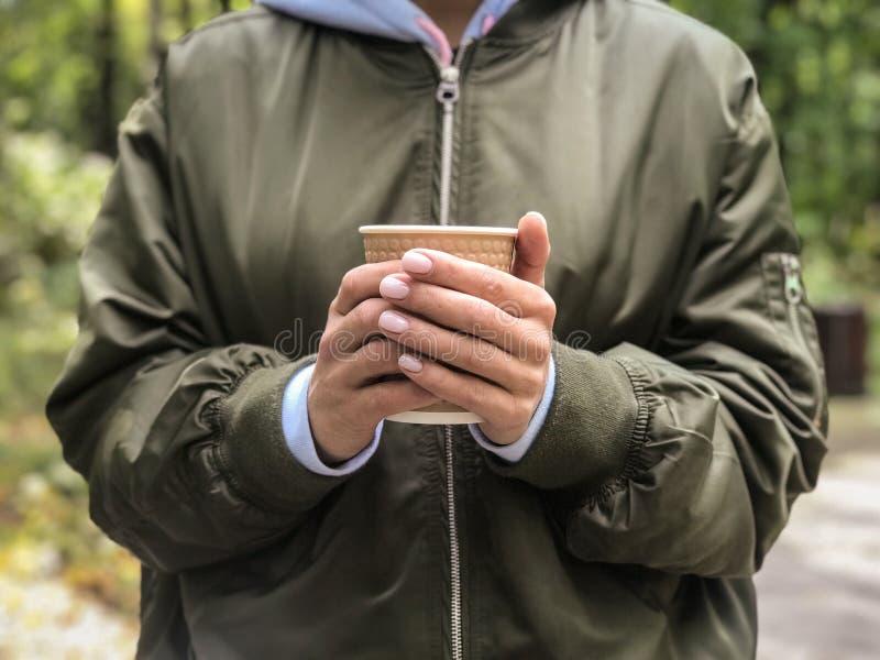 Tasse de café chez la main de la femme en parc photo libre de droits