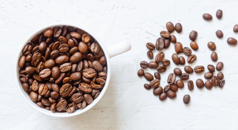 Tasse de café complètement de grains de café sur le fond blanc photo stock