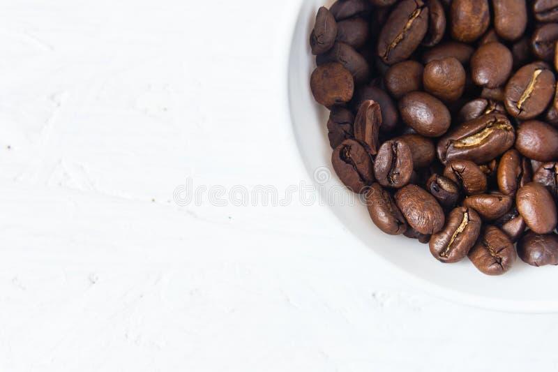 Tasse de café complètement de grains de café sur le fond blanc photographie stock libre de droits