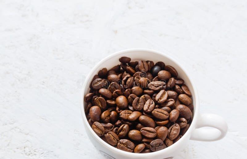 Tasse de café complètement de grains de café sur le fond blanc photographie stock