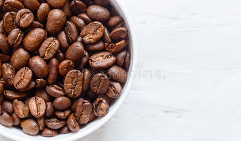 Tasse de café complètement de grains de café sur le fond blanc image libre de droits