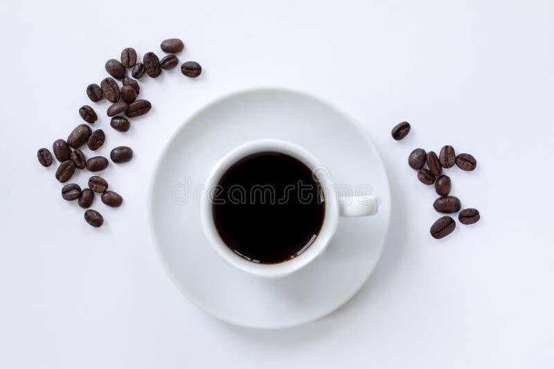 Tasse de café d'expresso avec la soucoupe et les grains de café dispersés autour sur le fond blanc Vue sup?rieure Fermez-vous ver photographie stock