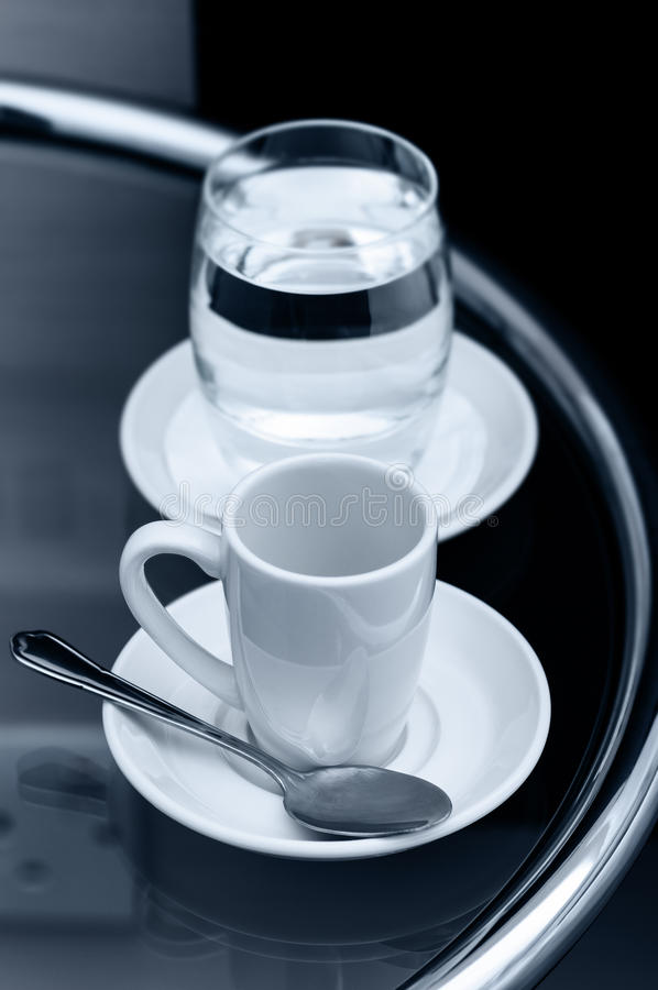Tasse de café d'expresso et verre vides de l'eau sur le plan rapproché de table de chevet image stock