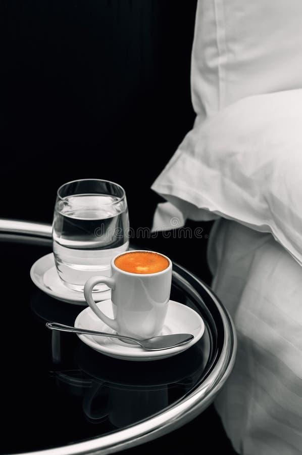 Tasse de café d'expresso pleins et verre de l'eau sur le plan rapproché de table de chevet photo stock