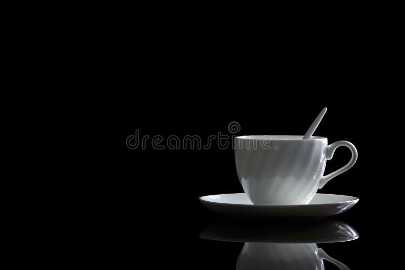 Tasse de café dans le contre-jour sur un fond réfléchi noir photos libres de droits
