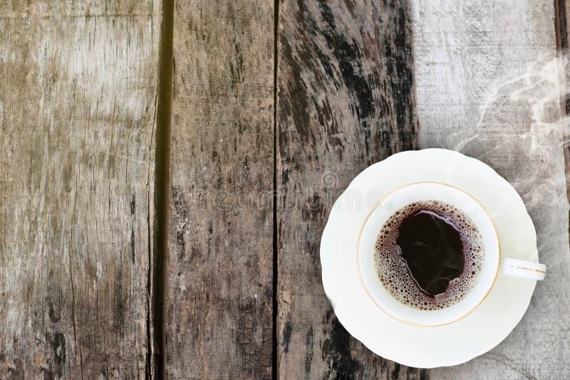 Tasse de café dans le matin sur le vieux fond en bois photographie stock libre de droits