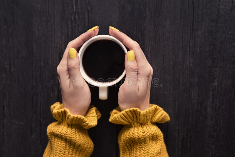 Tasse de café dans mains femelles Fond en bois Vue supérieure image stock