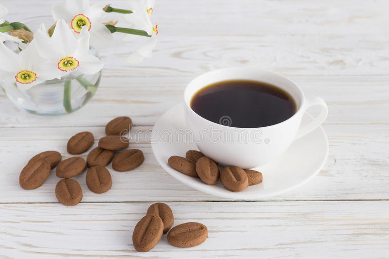 Tasse de café, de biscuits et de narcisse sur le fond en bois blanc photos libres de droits
