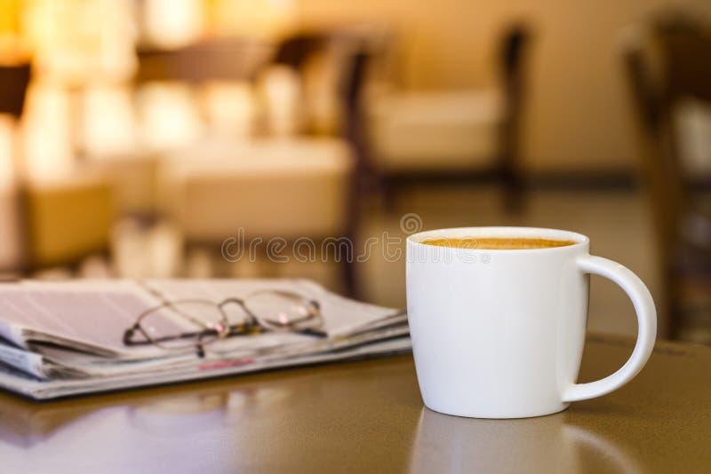 Tasse de café de cappuccino sur la table en bois avec le journal images libres de droits