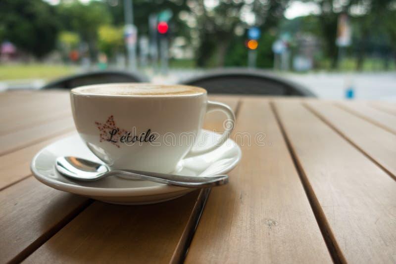 Tasse de café de Cappucino avec le fond brouillé de ville image libre de droits