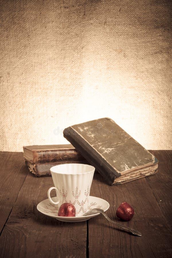 Tasse de café, de shokolad et de pile de vieux livres sur le vieil en bois photos libres de droits