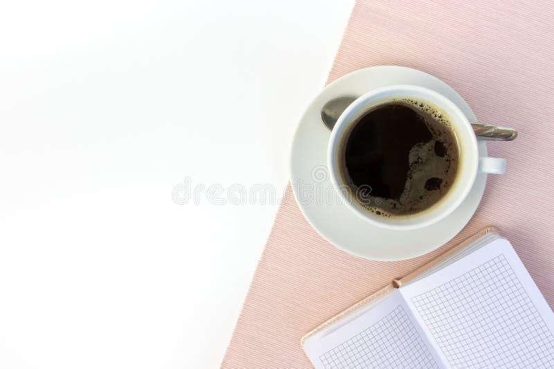 Tasse de café en céramique blanche et, carnet sur la table blanche, couverte de tissu rose avec l'espace de copie images libres de droits