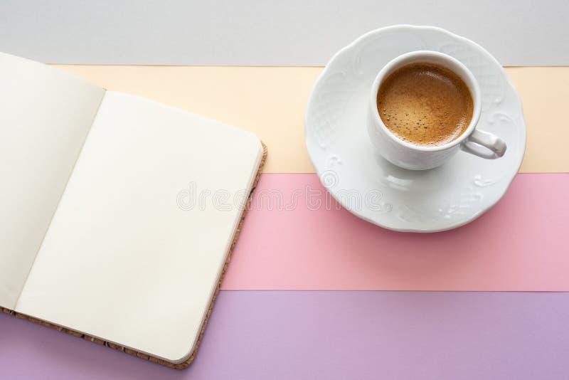Tasse de café et de carnet avec l'espace pour le texte sur le fond de couleur en pastel photo stock