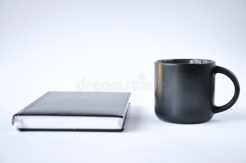 Tasse de café et de carnet sur le fond blanc photographie stock