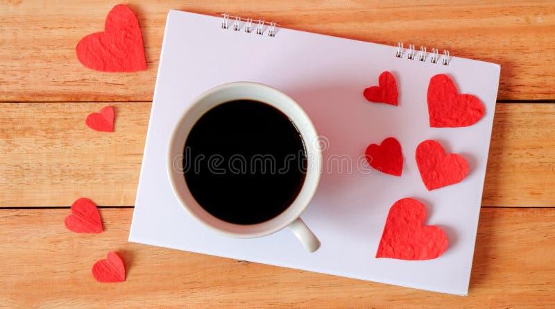 Tasse de café et de coeurs sur un fond en bois Le café calen dessus images stock