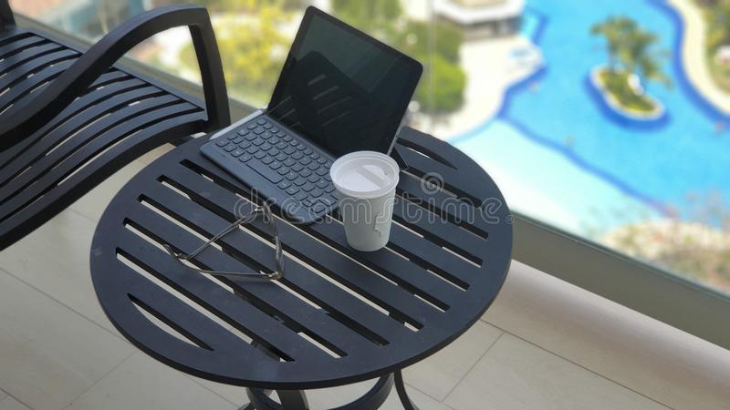 Tasse de café et de comprimé dans un balcon pendant des vacances photos stock