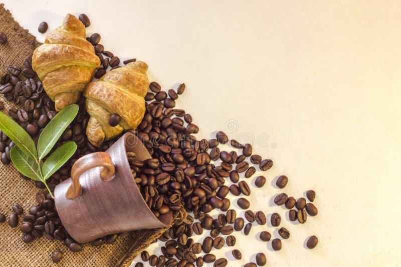 Tasse de café et croissant sur les haricots et le fond blanc image libre de droits