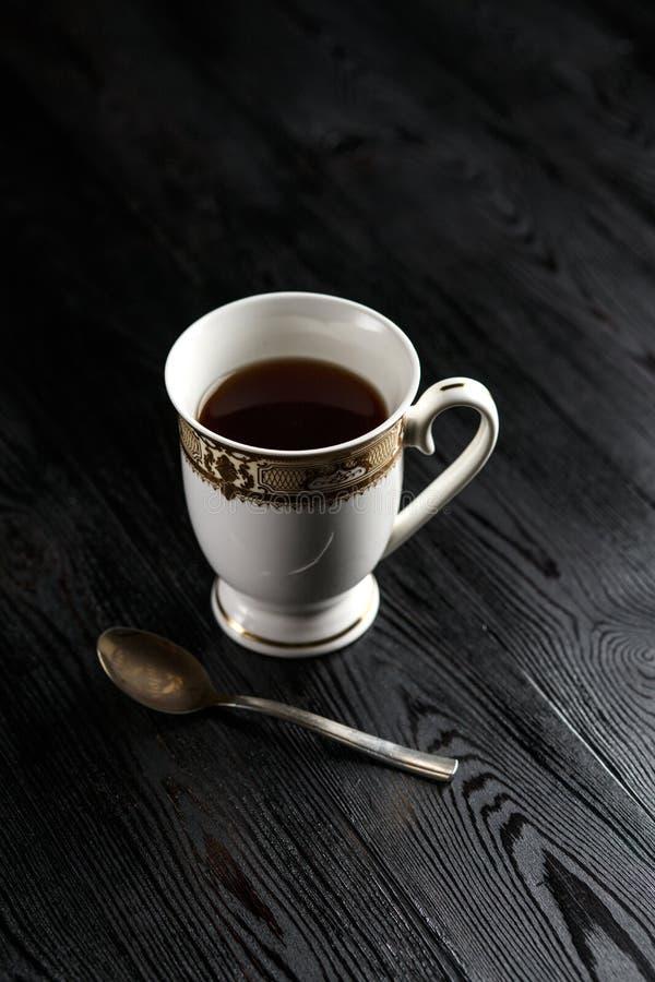 Tasse de café et de cuillère sur un fond foncé photo libre de droits