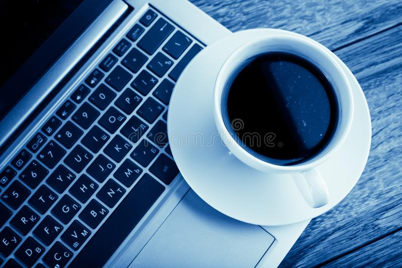 Tasse de café et d'ordinateur portable sur la table en bois image stock