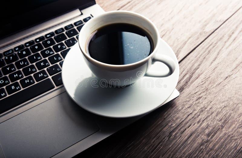 Tasse de café et d'ordinateur portable sur la table en bois photographie stock
