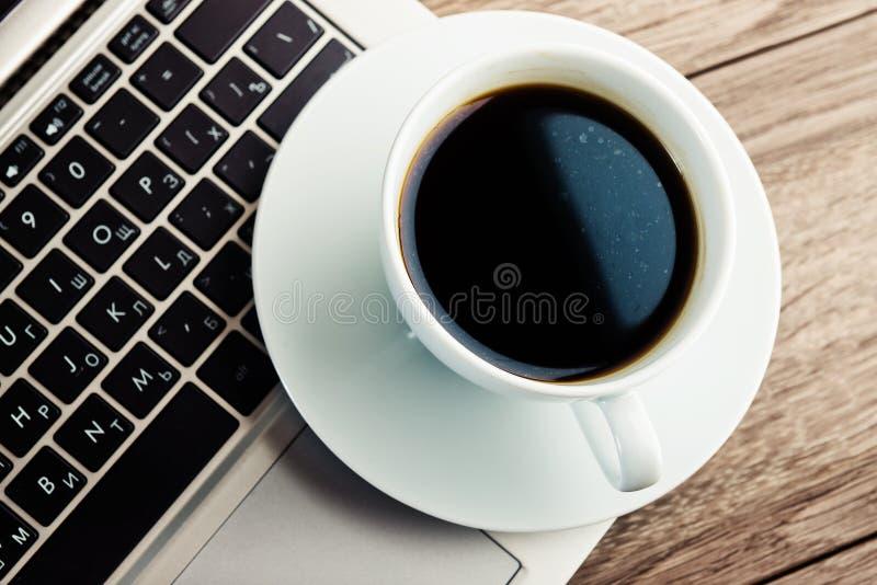 Tasse de café et d'ordinateur portable sur la table en bois photos libres de droits
