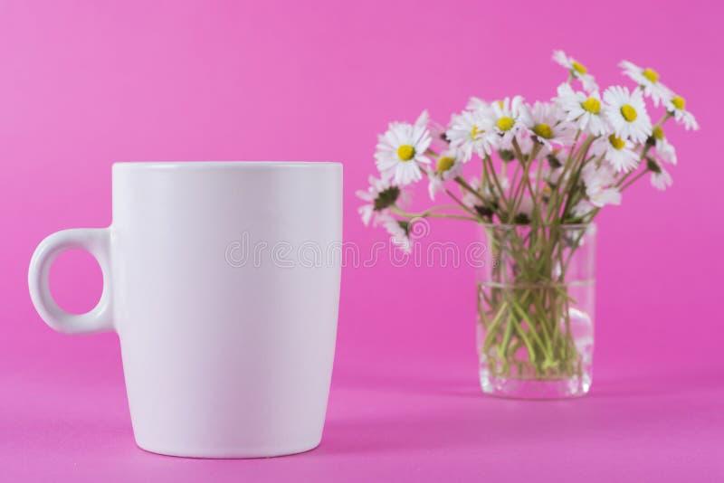 Tasse de café et de fleur brouillée de marguerite de mouvement dans le rose photographie stock libre de droits