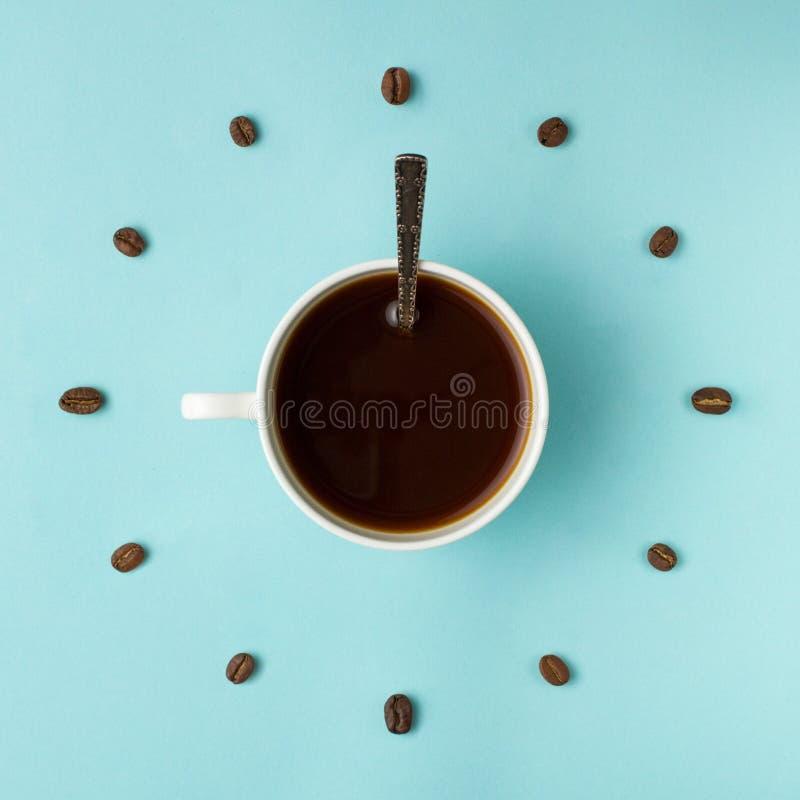 Tasse de café et haricots rôtis disposés comme visage d'horloge sur le fond bleu, vue supérieure Symbole de temps de café Énergie photo stock